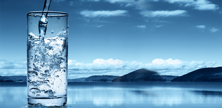 Image of still water being poured in a glass; compare still to sparkling water.